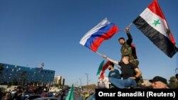 Сирийцы размахивают сирийскими и российскими флагами, протестуя против ракетных ударов США и их союзников. Дамаск, 14 апреля 2018 г.