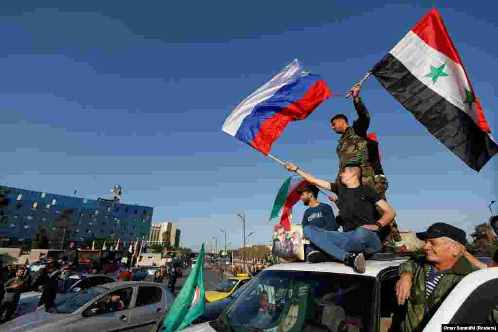 Прихильники президента Сирії Башара Асада із сирійськими і російським прапорами висловлюють своє обурення операцією союзників
