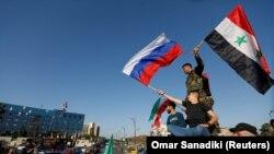 Сирийцы размахивают сирийскими и российскими флагами, протестуя против ракетных ударов США и их союзников, 14 апреля 2018