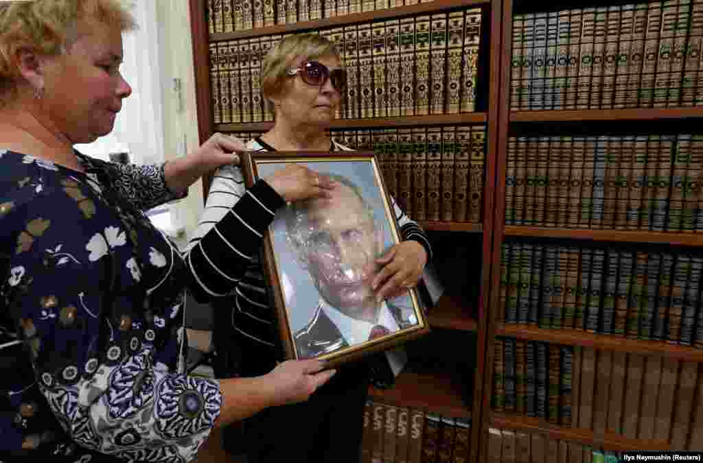 An employee helps a visitor to explore a tactile image of Russian President Vladimir Putin at a specialized library for blind and partially sighted people in Krasnoyarsk. (Reuters/Ilya Naymushin)