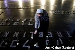 Жінка кладе квіти у Залі пам'яті у Всесвітнього центру пам'яті Голокосту Яд Вашем