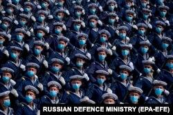 Disa ushtarë me maska përgjatë një parade.