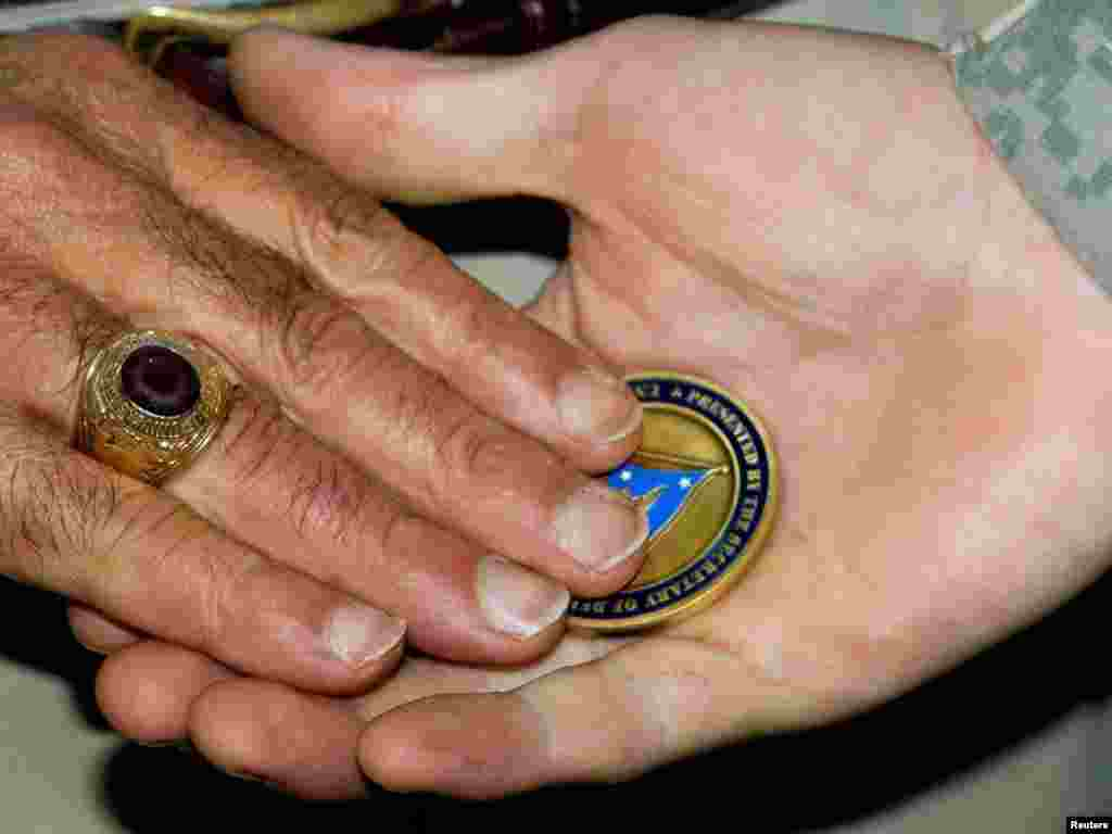 "U.S. Defense Secretary Leon Panetta places a ""challenge coin"" in the palm of a U.S. soldier during a ceremony where he presented more than 150 such coins to troops at Camp Victory in Baghdad.Photo by Paul J. Richards for Reuters"