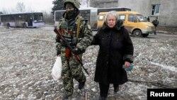 Украинский военнослужащий помогает пожилой женщине донести пакет с гуманитарной помощью. Дебальцево, 6 февраля 2015 года.