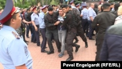 Kazakh police detain RFE/RL reporter Pyotr Trotsenko near the site of a protest against the presidential election in Almaty on June 9.