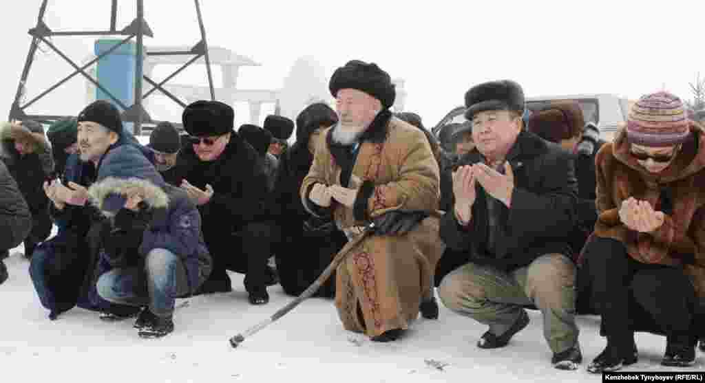 Родные и соратники Алтынбека Сарсенбаева читают молитву на его могиле в день шестой годовщины со дня гибели политика. Алматы, 11 февраля 2012 года.