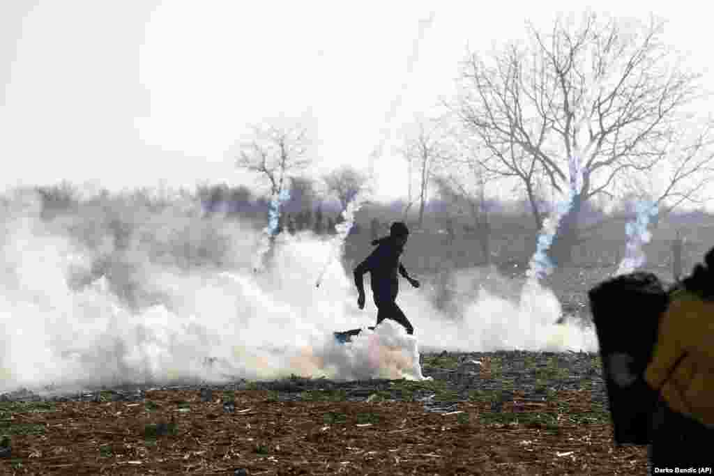 Мигрант убегает от слезоточивого газа, который применила греческая полиция во время столкновения на пограничном пункте Пазаркуле 2 марта.