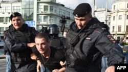 Russian security detain a man following a rally calling for fair elections in central Moscow in August last yeat.