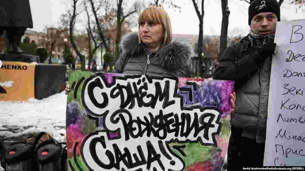 Мама Александра Лариса Кольченко держит плакат «С днем рождения, Саша»