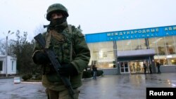 An armed man patrols outside the airport in Simferopol, Crimea's capital, on February 28.