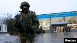 An armed man patrols outside the airport in Simferopol, Crimea's capital, on February 28.
