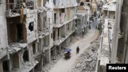 Residents walk near damaged buildings in the rebel-held area of Old Aleppo on May 5.