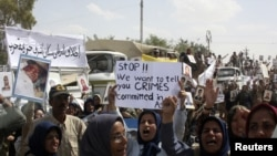 Residents of Camp Ashraf demonstrate in front of reporters touring in a bus on April 9, a day after their clashes with the Iraqi security forces.