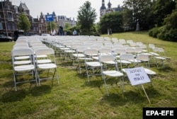 """298 пластиковых кресел, поставленных как в салоне """"Боинга"""", и плакат, оставленные близкими погибших на рейсе MH17 в знак протеста перед посольством России в Гааге. 18 мая 2018 года"""