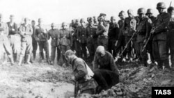 In this photo from 1941, Soviet prisoners dig their own graves as German soldiers look on impassively.