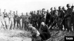 Тұтқынға түскен совет жауынгерлері өз көрін өздері қазып жатыр. 11 қараша 1941 жыл.