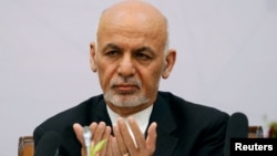 Afghan President Ashraf Ghani prays during a peace and security cooperation conference in Kabul on June 6.