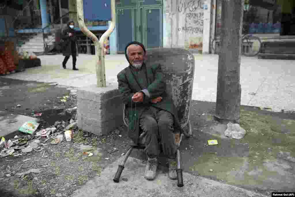 A laborer sits in his wheelbarrow as he waits for customers in the Afghan capital, Kabul. (AP/Rahmat Gul)