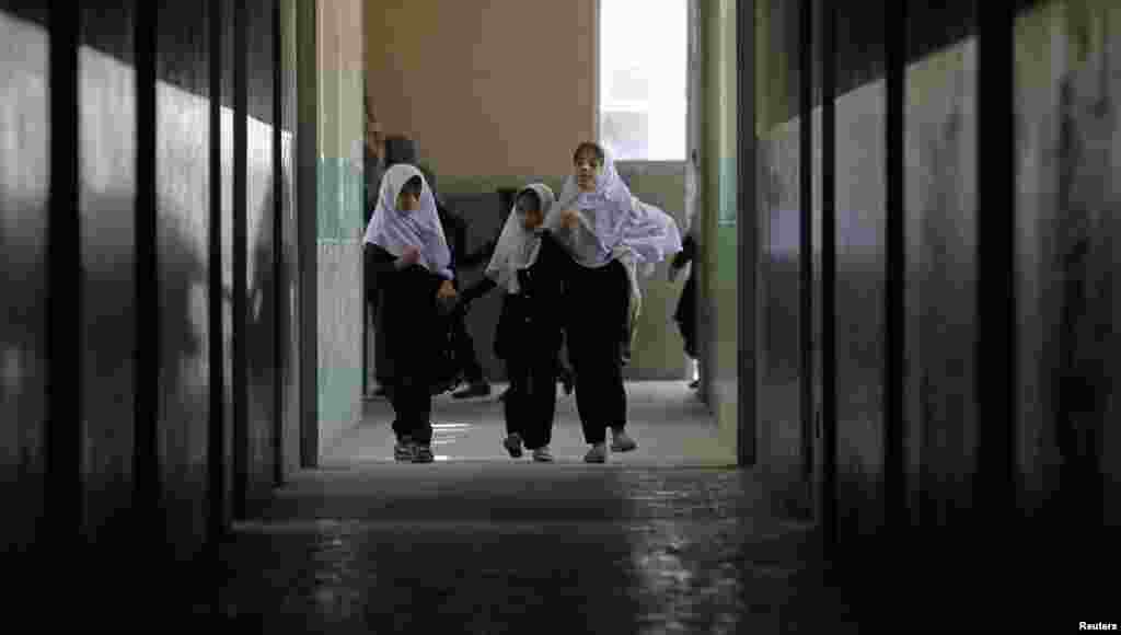 Blind students walk along a corridor at the school.