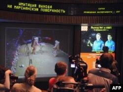 """Журналисттер """"Марс-500"""" миссиясынын мүчөлөрүнүн жасалма Марстын бетине чыгуусун экрандан көрүшүүдө. Москванын четиндеги Королев атындагы Орбиталдык миссияны контролдоо борбору, 14-февраль, 2011"""
