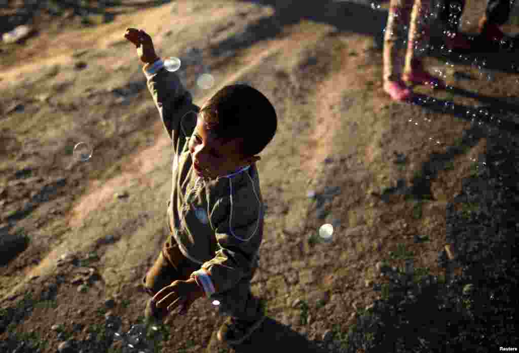 A child plays with soap bubbles at a makeshift camp for migrants and refugees at the Greek-Macedonian border near the village of Idomeni, Greece. (Reuters/Stoyan Nenov)