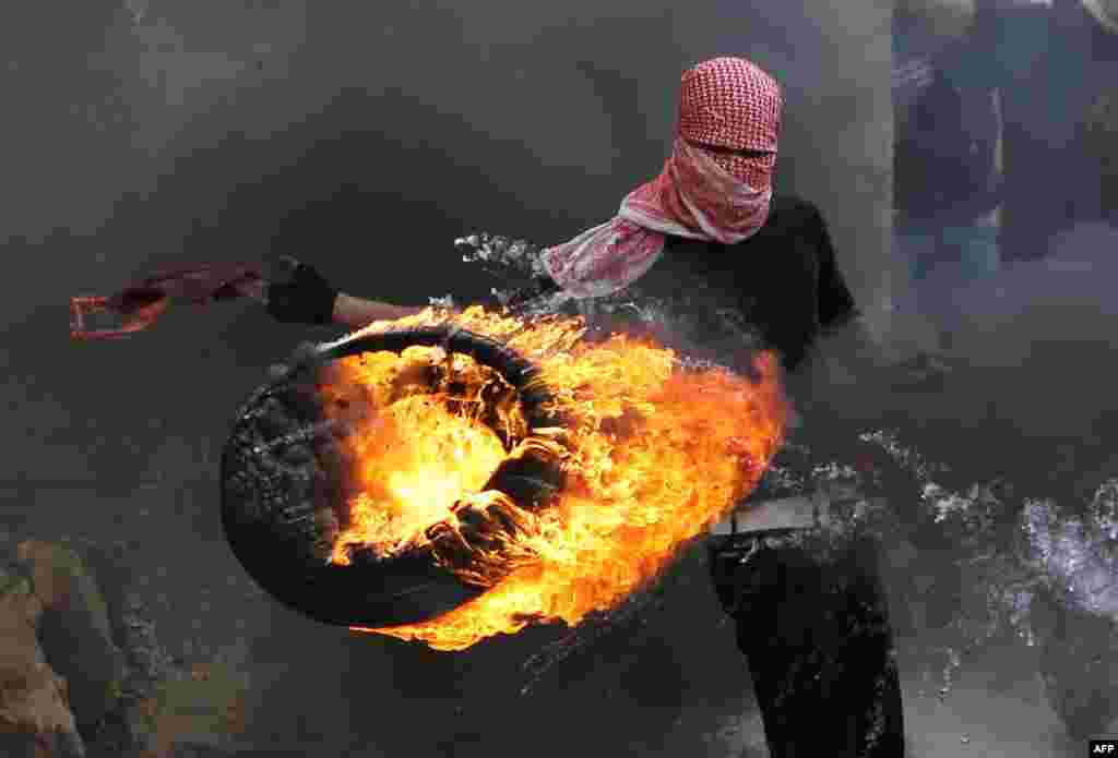 A Palestinian sets fire to a tire during clashes between hundreds of Palestinians and Israeli soldiers after a march marking the 65th Nakba day or Day of Catastrophe on May 15 in Betunia near the West Bank city of Ramallah. (AFP/Abbas Momani)