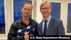 Michael White, a freed U.S. Navy veteran detained in Iran since 2018, poses with U.S. Special Envoy for Iran Brian Hook while on his return to the United States at Zurich Airport in Zurich, June 4, 2020