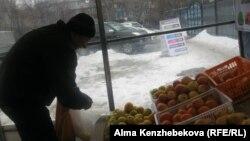 Покупатель Владимир Кузнецов в торговой палатке. Алматы, 7 марта 2014 года.