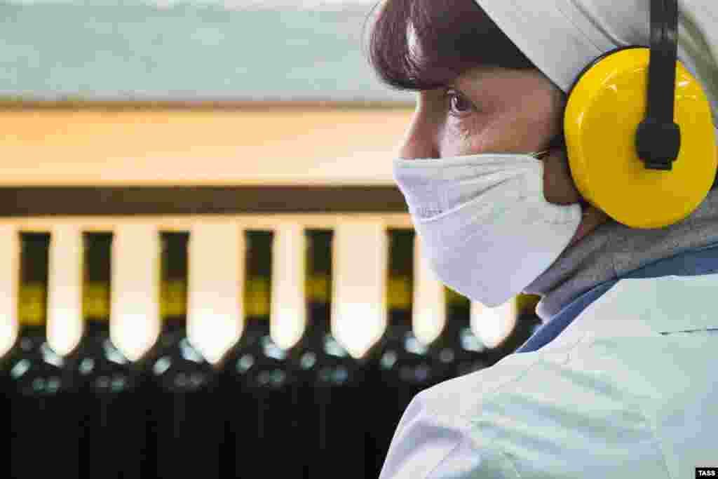 Через високий попит на маски і їхню дорожнечу деякі кримчани вдаються до використання саморобних марлевих масок. Вони не захищають від вірусу, а просто встановлюють бар'єр між людьми На фото: співробітниця в цеху розливу вина на заводі «Массандра»