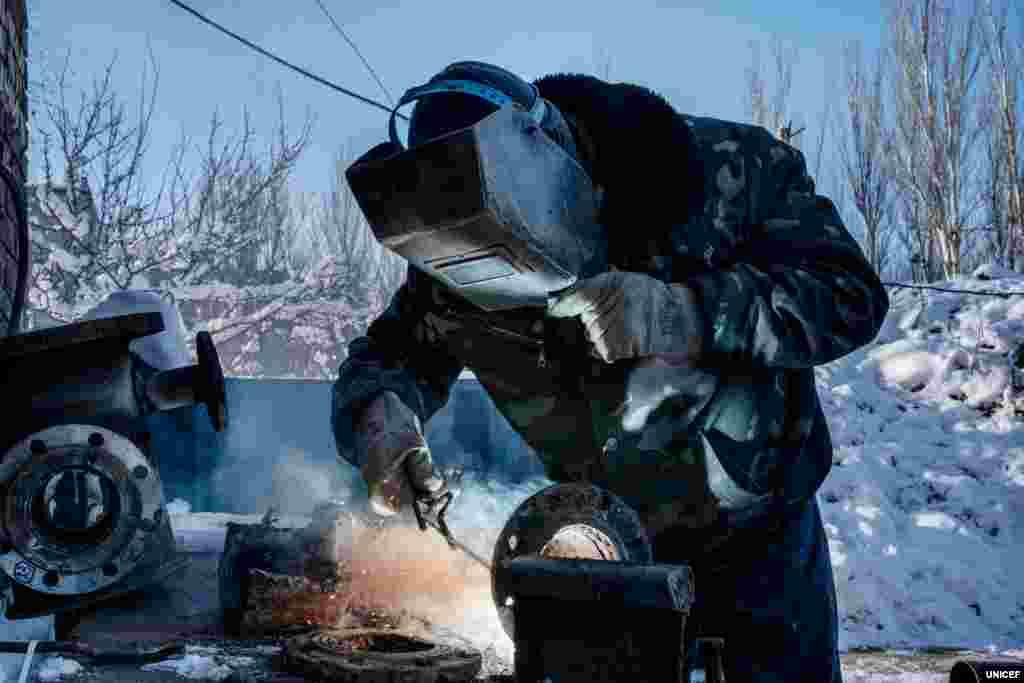 Загалом із початку конфлікту в Україні понад 30 працівників об'єктів системи водопостачання були вбиті або зазнали поранень. Лише у 2018 році на сході України було зафіксовано 89 нападів на об'єкти системи водопостачання. Ще 19 таких випадків було зафіксовано вже за перші три місяці 2019 року. На фото 59-річний Анатолій Сотников, працівник компанії «Вода Донбасу», зварює шматки сталі, щоб можна було використати стару трубу для ремонту пошкодженої ділянки водопроводу.