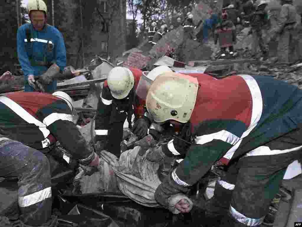 Rescue workers pull out the body of a victim from the ruins of an apartment building on September 13, 1999.