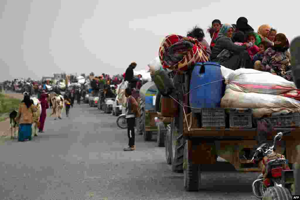Displaced Syrians arrive in the village of Suwaidiya Saghira, north of Tabqa, on March 30. (AFP/Delil Souleiman)