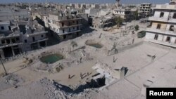 Syria -- A still image taken on September 27, 2016 from a drone footage obtained by Reuters shows people standing near craters and damaged buildings in a rebel-held area of Aleppo,