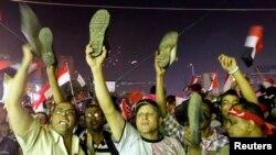 Президент Мухаммед Мурсинин сөзүнөн кийин анын каршылары бут кийимдерин булгап, нааразылыгын билдиришүүдө. Каирдин Тахрир аянты. 3-июль 2013.