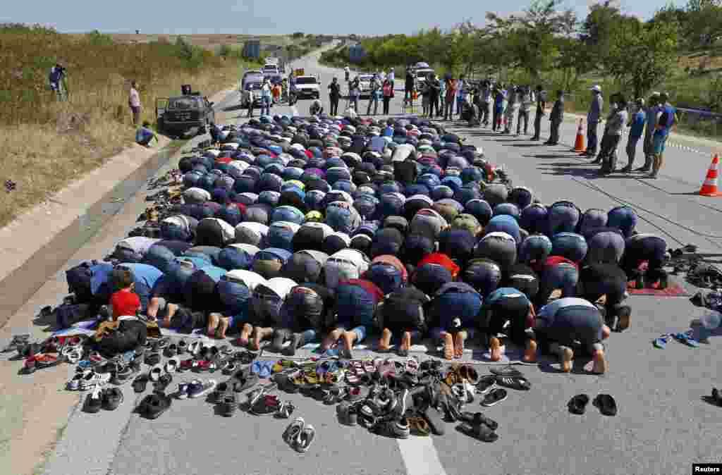 Migrants pray on a highway near Edirne, Turkey. (Reuters/Osman Orsal)