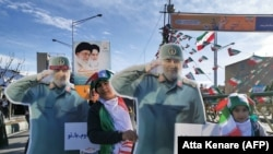 Iranian children carry a cardboard cutout of slain Iranian General Qasem Soleimani, on the 40th day of his killing in a US drone strike, during commemorations marking 41 years since the Islamic Revolution, in Tehran, February 11, 2020