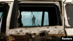 An Afghan policeman is seen through a damaged vehicle, which was hit in a suicide attack in Kabul in October.