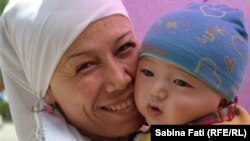 O mamă uigură cu copilul ei la Turfan