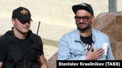 Russian theater and film director Kirill Serebrennikov (right), is escorted outside Moscow's Basmanny district court after a hearing on August 12.