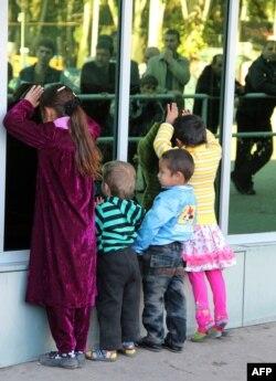 Дети ждут в аэропорту прилета самолета из России. Душанбе, 2 ноября 2013 года.