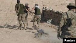 Иракские спецназовцы тянут тело джихадиста, чтобы отдать его жителям ближайшей деревни для захоронения. 11 ноября 2016