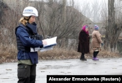 A monitor from the OSCE works in the settlement of Holubivske in the Luhansk region that has been affected by fighting.