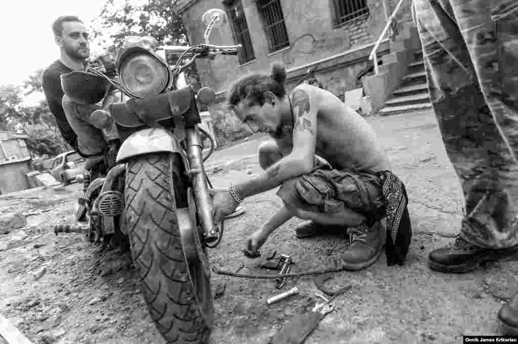 A member of the Cross Riders MC repairing one of their bikes. Locals didn't object to the bikers locating their clubhouse in their neighborhood, but they did mind the noise of the motorcycles. The Cross Riders will move to a new location at the end of the month.