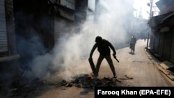 An Indian policeman puts out a bonfire at a road block in Srinagar on October 29.