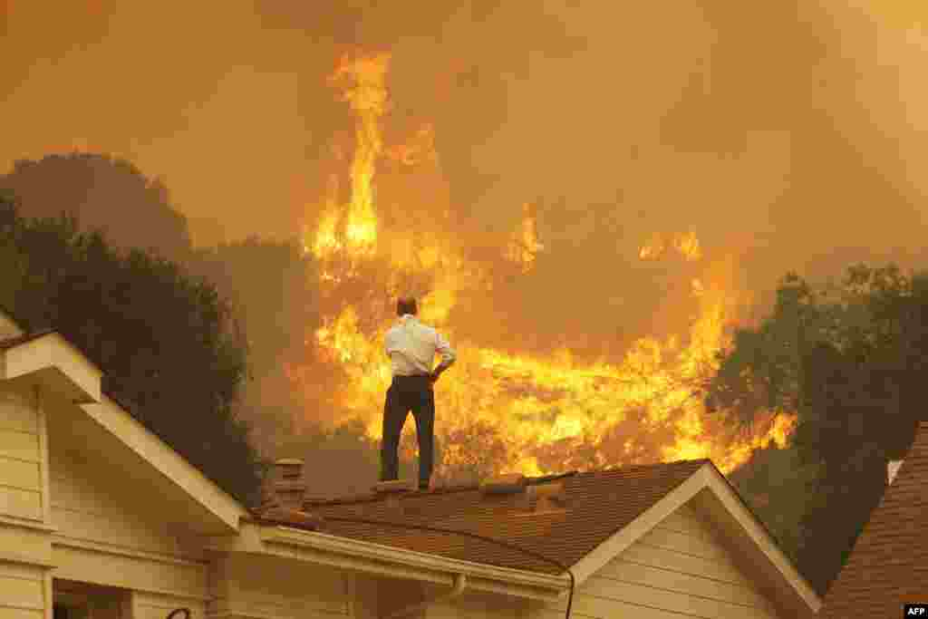 A man on a rooftop looks at the approaching flames of a massive wildfire near Camarillo, California. (Getty Images/David McNew)