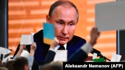 Russian President Vladimir Putin is seen on a large screen as he speaks during his annual press conference in Moscow on December 19.
