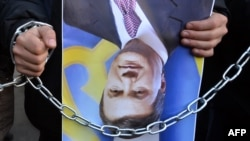 Демонстрант носи превртен портрет на претседателот Јанукович.