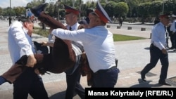 A protester is arrested in Almaty.
