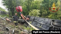A firefighter stands next to an overturned tourist bus that crashed in Italy's Tuscany region on May 22.