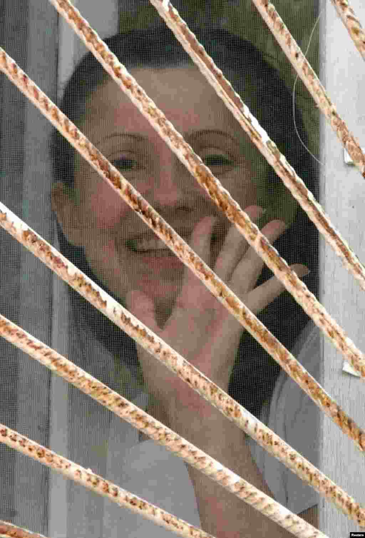 """Юлия Тимошенко машет из окна больничной палаты в одной из киевских больниц. Она проходила здесь лечение после ареста 13 февраля 2001 года по обвинению в уклонении от уплаты налогов в особо крупном размере, когда она в 1995–1997 годах возглавляла госкомпанию """"Единые энергетические системы Украины"""". Многие сторонники политика считали, что арест имел политический подтекст: Тимошенко была оппонентом в то время президента Леонида Кучмы. Суд впоследствии признал обвинения в отношении нее несостоятельными. Киев, 31 марта 2001 года"""